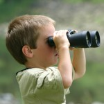 boy looking through binoculars